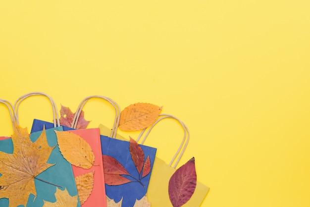 Borse della spesa artigianali circondate da foglie autunnali gialle e arancioni
