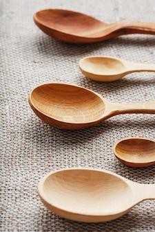 Cucchiai artigianali realizzati con diversi tipi di legno giacciono in fila su un tessuto di tela di canapa. vista dall'alto, spazio libero