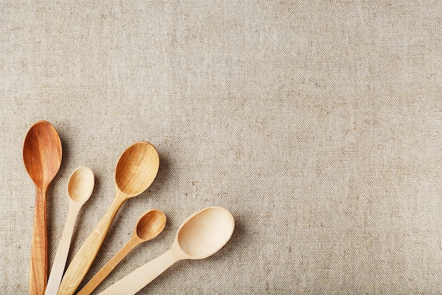 Cucchiai artigianali realizzati con diversi tipi di legno giacciono in fila su un tessuto di tela di canapa