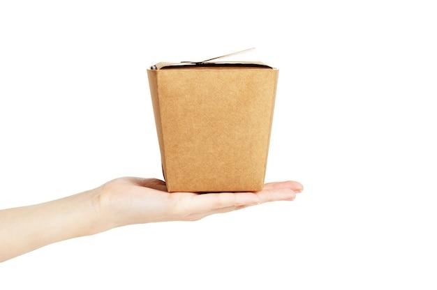 Scatola quadrata artigianale per la consegna del cibo in una mano femminile su sfondo bianco. imballaggio di cartone vuoto per l'iscrizione. copia spazio, modello. materiale di imballaggio.