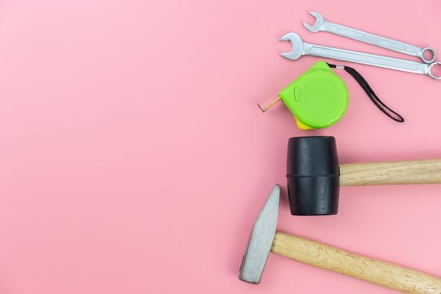 Gruppo di strumenti del mestiere sopraelevato su fondo pastello rosa