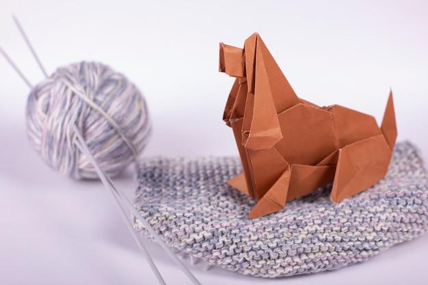 Concetto di origami artigianale di una casa accogliente - un cane con gomitoli di lana si siede su una sferza. fine fatta a mano della carta patinata su