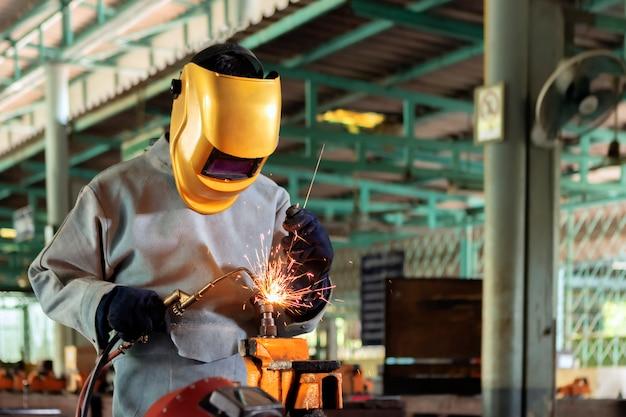 Un artigiano sta saldando con un pezzo in acciaio. persona che lavora sull'acciaio per saldatore usando la saldatrice elettrica ci sono linee di luce che fuoriescono e attrezzature di sicurezza nell'industria industriale.