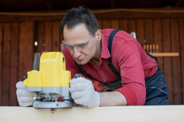 Falegname artigiano lavora sul pezzo in legno con utensile di fresatura si chiuda al laboratorio di cottage