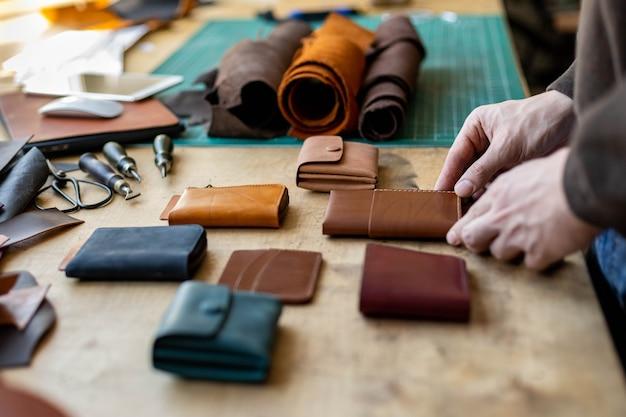 Mani dell'artigiano che stendono la pelletteria sul tavolo di legno agli accessori per il lavoro manuale dell'officina in pelle