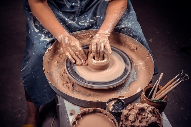 Mani di artigiano e tornio da vasaio Foto Premium