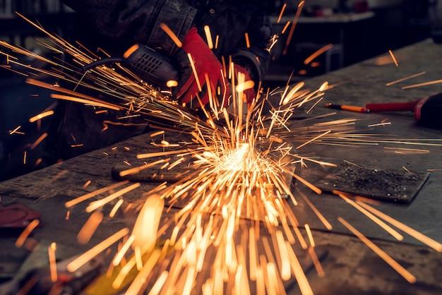 Artigiano che sega metallo, brilla intorno all'officina