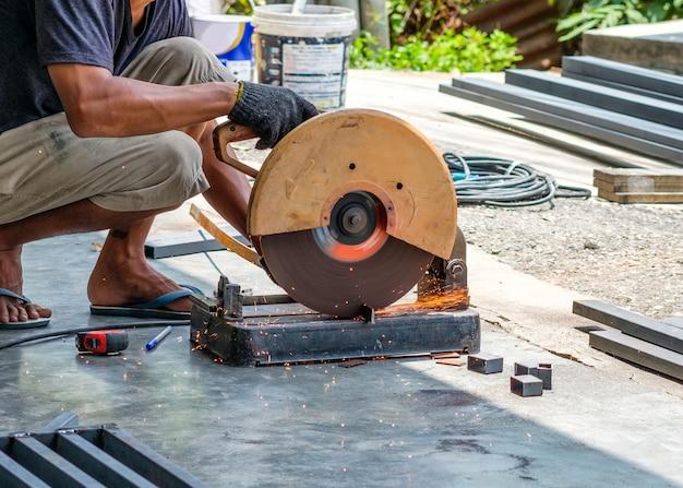 Artigiano che sega l'acciaio con mola a disco e scintille
