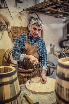L'artigiano usa il compasso da disegno per misurare il fondo di un barile di legno realizzato nel suo laboratorio.