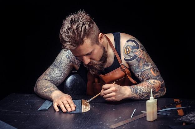 L'artigiano che lavora con la pelle taglia la pelletteria nel negozio di conciatori