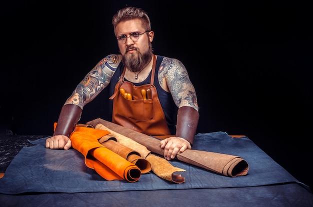 L'artigiano che lavora con la pelle lavora con la pelle./ l'uomo della pelle crea una nuova lavorazione della pelle nel suo negozio.