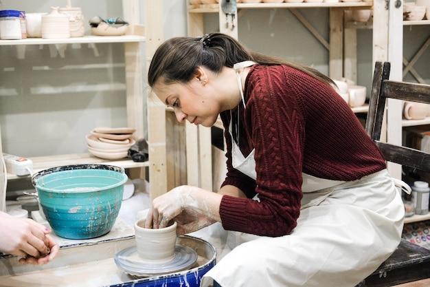 Artigiana nel laboratorio di ceramica fa una tazza su un tornio da vasaio