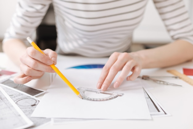 Dita astute. abile ingegnere professionista femminile che utilizza il goniometro e lavora al progetto mentre era seduto al tavolo
