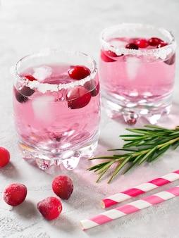 Cocktail di mirtilli rossi con ghiaccio, frutti di bosco e rosmarino su bianco