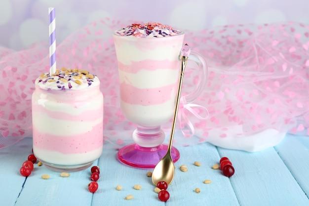 Dessert al latte di mirtillo rosso in barattolo di vetro e vetro, su tavolo in legno colorato
