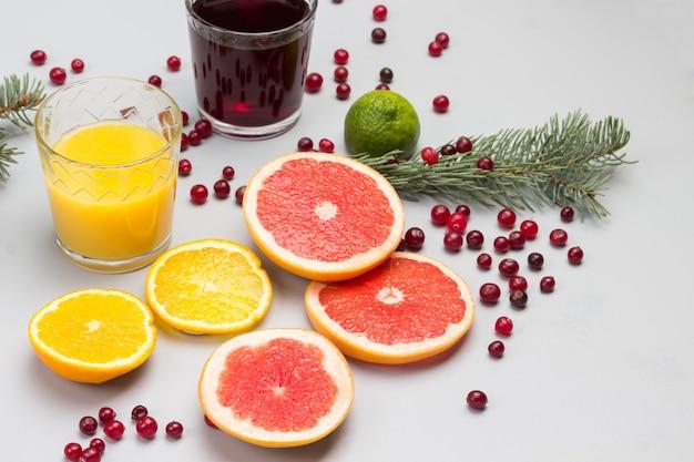 Bevande al mirtillo rosso e arancia in bicchieri. fette di arancia, pompelmo e mirtilli rossi, rametti di abete sul tavolo.