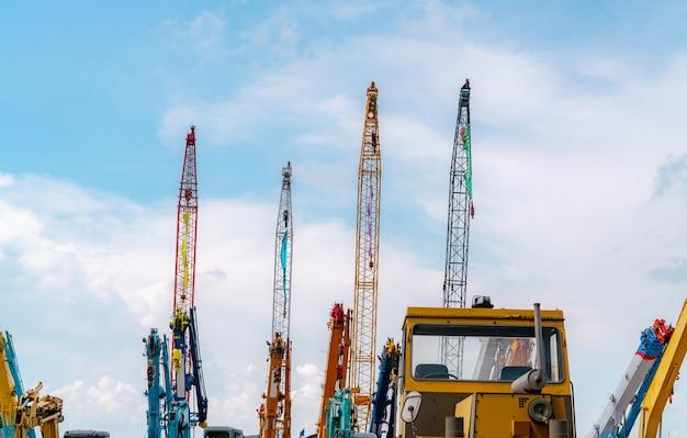 Gru contro il cielo blu e nuvole bianche. settore immobiliare. le gru cingolate rosse e gialle utilizzano attrezzature per il sollevamento delle bobine. gru in affitto presso l'area di parcheggio. concessionaria gru per impresa edile.