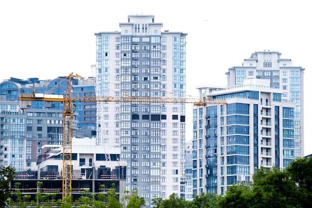 Gru in un cantiere edile di un moderno quartiere residenziale edifici di appartamenti alti o grattacieli in un nuovo complesso di élite.