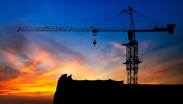 Gru per attrezzatura da cantiere su sfondo tramonto con tracciato di ritaglio