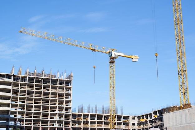 Gru e cantiere all'esterno. edificio multipiano in costruzione, ponteggi, cemento e due gru.