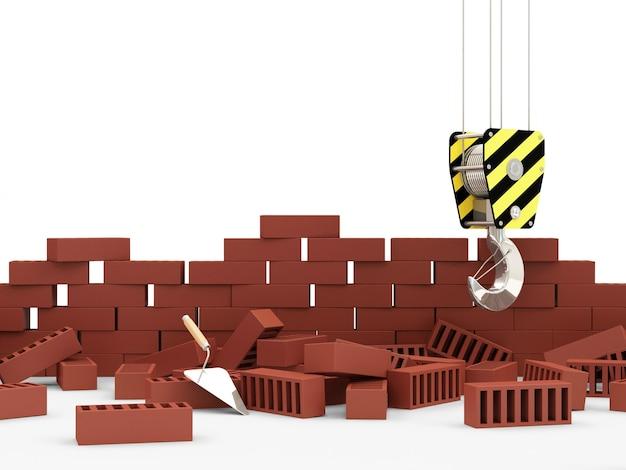Gancio della gru vicino al muro di mattoni in costruzione