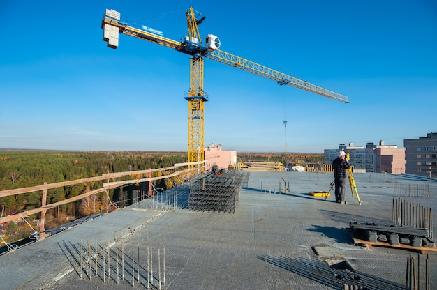 Gru di una nuova casa monolitica in costruzione contro il cielo blu