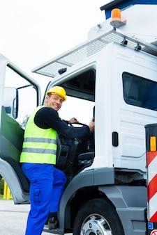 Operatore della gru che guida con il camion del cantiere
