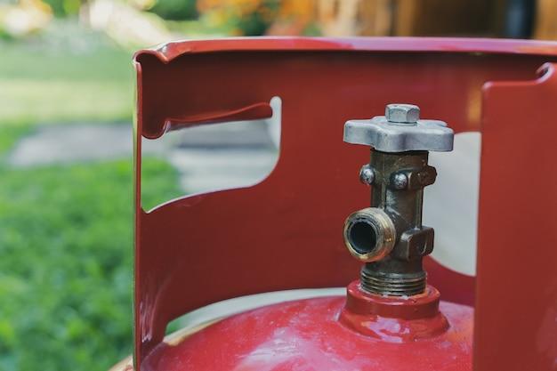 La gru di una bombola di gas portatile e portatile di colore rosso ravvicinato sullo sfondo di un giardino con erba verde.