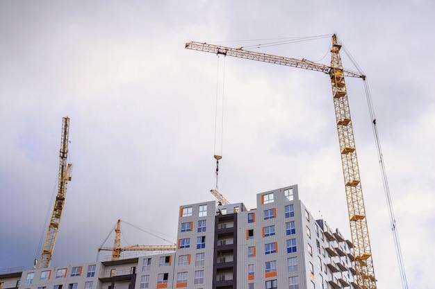 Gru e costruzione di edifici sullo sfondo di un cielo nuvoloso