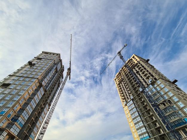 Gru in piedi vicino a edifici multipiano in costruzione sullo sfondo del fondo del cielo blu ...
