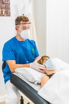 Massaggio cranico sulla testa di un fisioterapista con misure protettive per un paziente in barella. pandemia di covid19. osteopatia, chiromassaggio terapeutico