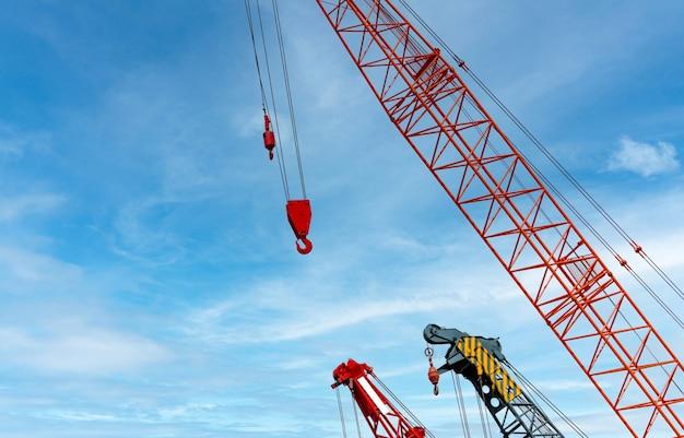 Gru cingolata contro il cielo blu e nuvole bianche. settore immobiliare. la gru cingolata rossa utilizza l'attrezzatura di sollevamento della bobina in cantiere. gru in affitto. concessionaria gru per impresa edile.