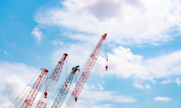 Gru cingolata contro il cielo blu e nuvole bianche industria immobiliare gru cingolata rossa