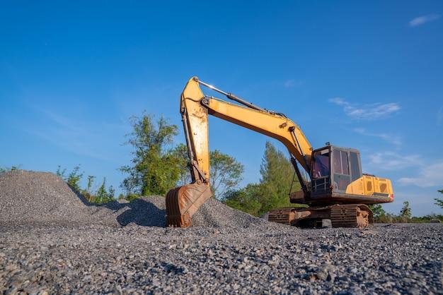 Escavatore cingolato che scava nel cantiere sul fondo del cielo blu