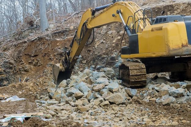 Un escavatore cingolato versa pietre grandi di un potente caricatore sovraccarica una pietra
