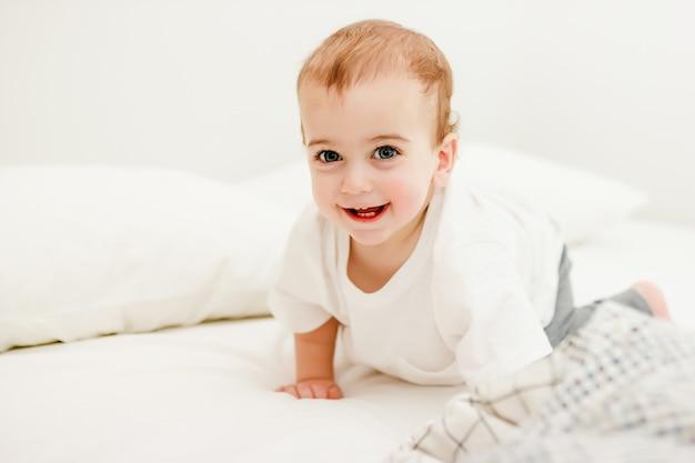 Bambino strisciante in maglietta bianca sul letto di casa