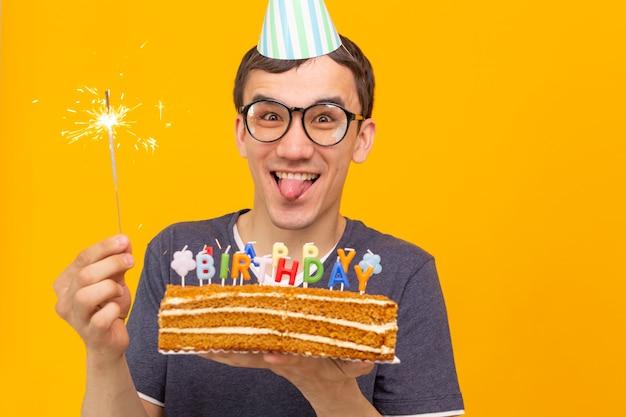 Pazzo giovane ragazzo allegro con gli occhiali che tiene una candela accesa nelle sue mani e una torta di congratulazioni su uno spazio giallo. concetto di celebrazione di compleanno e anniversario. spazio pubblicitario