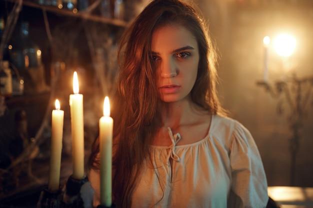 Donna demoniaca pazza con candela che sceglie pozioni, cacciata di demoni. esorcismo, mistero rituale paranormale, religione oscura, orrore notturno