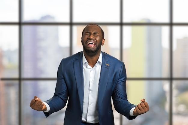 Uomo d'affari nero disperato pazzo piangendo. gridando e piangendo uomo in abiti da cerimonia in piena disperazione con i pugni alzati.