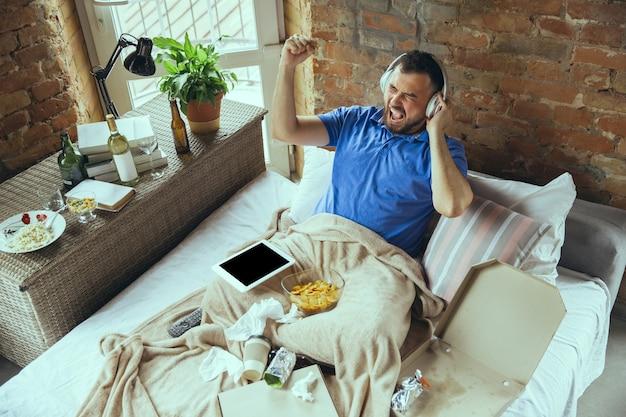 Guida pazza ascoltando musica e cantando uomo pigro che vive nel suo letto circondato da disordine