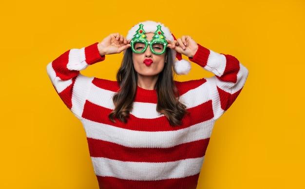 La bella donna moderna pazza ed eccitata con gli occhiali di natale divertenti e il cappello di babbo natale si diverte mentre posa contro un muro giallo