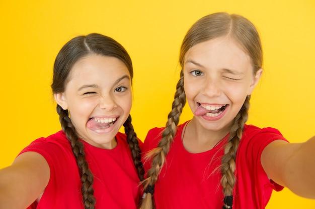Ragazze pazze. selfie per il blog. emozioni positive. ragazze selfie. piccole ragazze che fanno selfie sul telefono. divertirsi. sorellanza e amicizia. felice giorno dei bambini. felicità dell'infanzia. rete sociale.