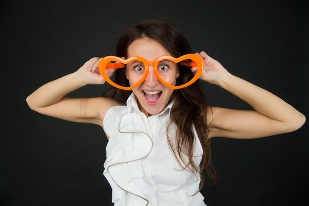 Pazzo d'amore. sorriso affascinante innamorarsi. gli occhiali a forma di cuore da ragazza celebrano il giorno di san valentino. ragazza pazza allegra sorridente viso cuore occhiali. simbolo di amore concetto. la donna graziosa si innamora.