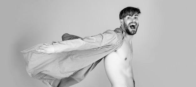Uomo pazzo in posa con il torso nudo sexy in pantaloni bianchi e veste aperta volante su sfondo grigio.