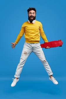 Uomo pazzo con longboard che salta in piedi