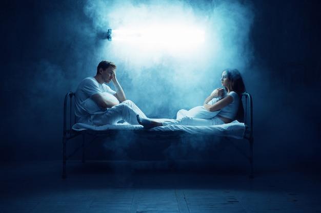 Uomo e donna pazzi sono seduti a letto, stanza buia .. psichedelici che hanno problemi ogni notte, depressione e stress, tristezza, ospedale psichiatrico