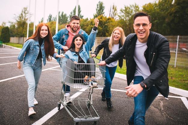Momenti pazzeschi. un gruppo di quattro giovani amici diversi in abito di jeans sembrano spensierati, giovani e felici camminando per le strade della città. moda di abiti urbani, libertà, amicizia, concetto di stile.
