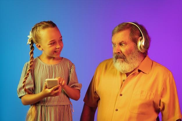 Musica pazza di giovane generazione. uomo anziano che trascorre del tempo felice con la nipote al neon. stile di vita anziano gioioso, famiglia, infanzia, concetto tecnologico. utilizzo di cuffie, smartphone. copyspace.