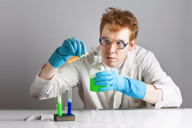 Il chimico pazzo dello scienziato dai capelli rossi mescola un pallone con il reagente.