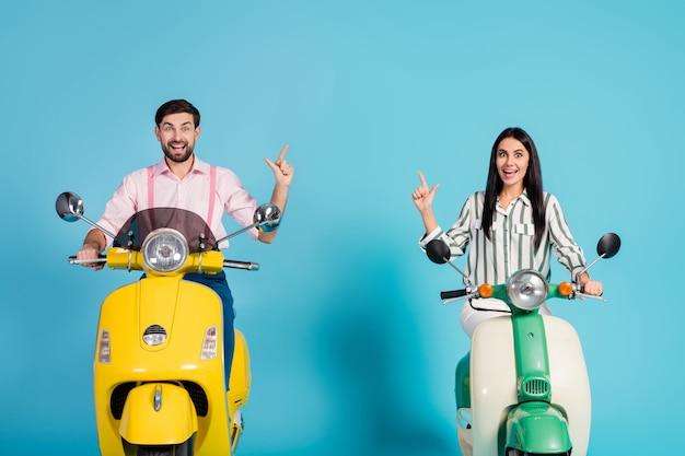 Pazzo sorpreso scioccato due persone motociclisti guidano la moto elettrica guarda annunci incredibili seguire punto dito indice copyspace urlo wow omg indossare camicia da cerimonia isolato su muro di colore blu